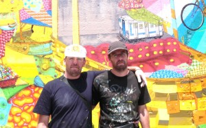 The bearded twins appear from the waist up, wearing ink-soaked T-shirts and caps. The one on the left has his arm around the other's shoulders. In the background, there is a wall with several multicolored graffiti