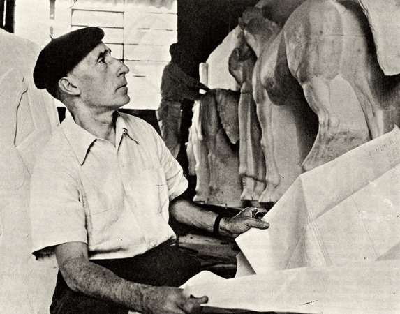 Old photo in black and white. Victor Brecheret sitting in the atelier, in a light shirt and dark beret, looks to the right toward the sculpture of a large horse. Holds the plan with the outline of the work.