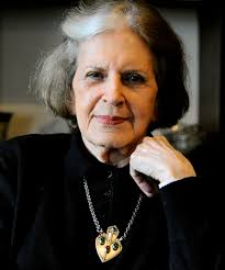 Elderly woman breast up, partially white hair, rests her face on her left hand. She wears a black blouse and a gold pendant necklace adorned with jewels.
