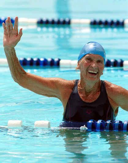 Elderly woman in a swimsuit and blue cap, inside the pool with water up to her waist, smiles and waves her right arm high up.