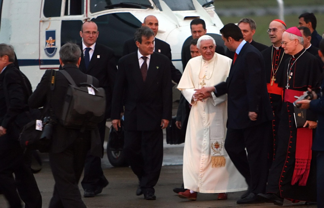 In the first plane, several men walking. To the right, 2 cardinals. In the center, the Pope in his white robes flanked by two men in dark suit. Behind, the front of a large helicopter.