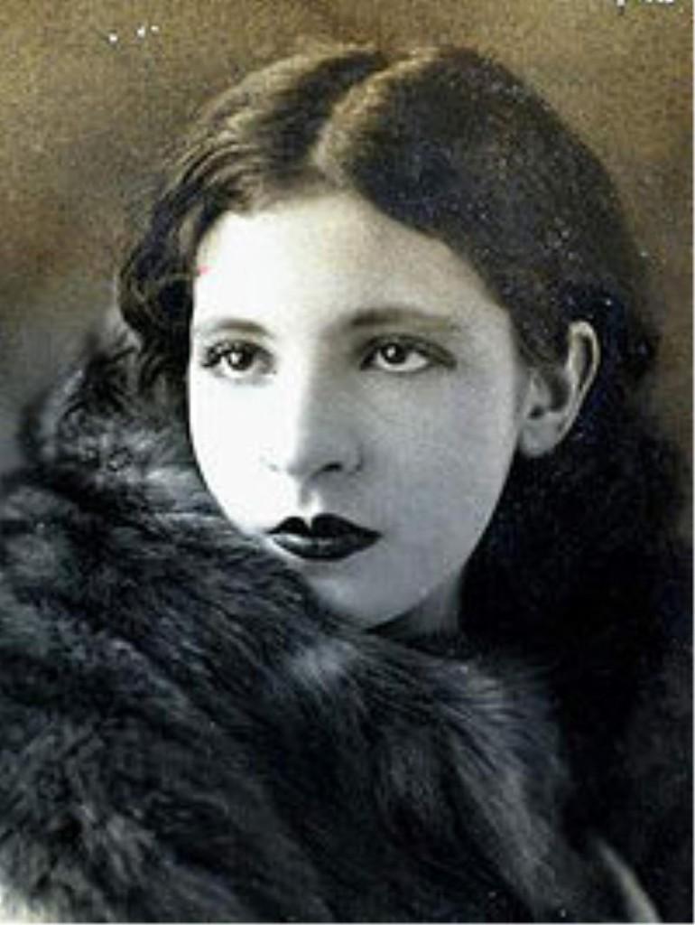 Pintura em preto e branco, retrata Pagu de lado do peito para cima, rosto virado para frente, vestindo um casaco de pele.