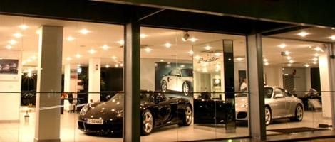 Vitrine de uma loja de automóveis de alto luxo, com interior todo bege claro e muito iluminado. Na frente, 2 carros esporte, um preto conversível e um prata coupê. Ao fundo, foto de carros luxuosos decoram as paredes.
