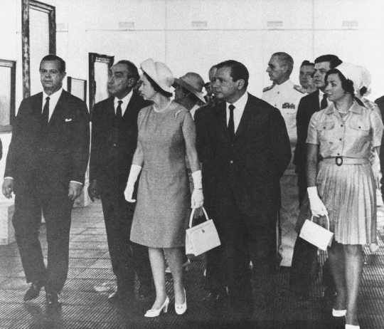 Black and white photo. Some people walking in a hall. Ahead, two women dressed in light-colored sober dresses and a hat, the Queen on the left. Behind, 4 men wear dark suits.