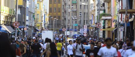 Rua de comércio popular com diversos prédios de lojas em ambos os lados, totalmente ocupada por milhares de pessoas, tanto nas calçadas como no meio da rua.