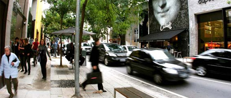 Calle de comercio repleta de tiendas de marca a ambos lados. A la izquierda, en una calzada bastante ancha, plana y adornada por algunos árboles, varias personas caminan, algunas portando bolsas de compras. A la derecha, varios coches viajan por la calle.