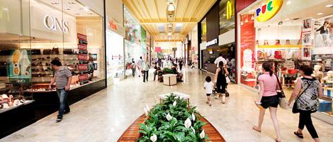 Parte interna del centro comercial. Corredor bastante largo con piso de piedra beige clara y muy pulido, por donde caminan varias personas. En los laterales, lado a lado hasta el final, varias tiendas. En el centro, bancos de madera de forma ovalada con un jardín de lirios blancos en el centro.