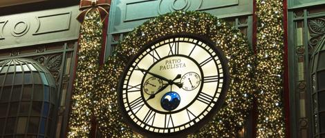 En la fachada de un centro comercial, un gran reloj redondo con números romanos y una esfera de cristal claro e iluminado detrás. En el centro, tiene en el lado derecho un pequeño cronómetro, en el lado izquierdo un pequeño cronógrafo y abajo un pequeño círculo de fondo azul oscuro muestra las fases de la luna. A su alrededor, rica decoración navideña.