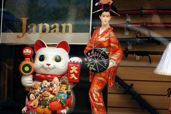 """Foto em close up da vitrine de uma loja. À direita, uma boneca japonesa veste traje típico de uma Gueixa – quimono de seda vermelho todo trabalhado com figuras douradas. Cabelos muito pretos compactados acima da cabeça e enfeitados por ornamentos de madeira e fitas vermelhas. Trás em uma das mãos uma pequena sobrinha aberta, preta e decorada com desenhos de flores cor de rosa. Atrás dela, um painel de madeira com diversas espadas japonesas penduradas. À esquerda, boneco do Maneki Neko, um dos amuletos do Japão mais famosos em todo o mundo, na forma de um gato branco sentado com um lenço vermelho ao redor do pescoço e uma armação no peito que trás figuras dos 7 Deuses da Sorte (fortuna e felicidade) no Xintoísmo), composta por várias figuras humanas multicoloridas em alto relevo. Em cada uma das mãos, o gato segura um amuleto da sorte. Atrás dele, um painel de vidro com a palavra """"Japan"""" pintada em letra douradas."""