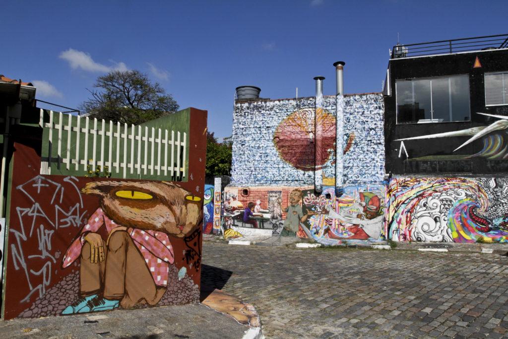 Imagens de um beco com as paredes das casas todas cobertas por grafites multicoloridos, sob um céu muito azul sem nuvens.