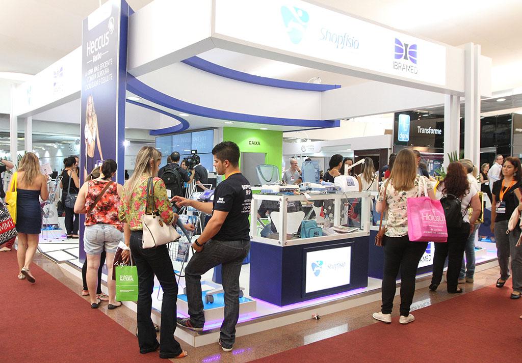 Estande de vendas todo branco com detalhes em azul escuro e alguma pessoas trabalhando em seu interior. Ao redor, diversos visitantes caminham sobre um carpete vermelho.