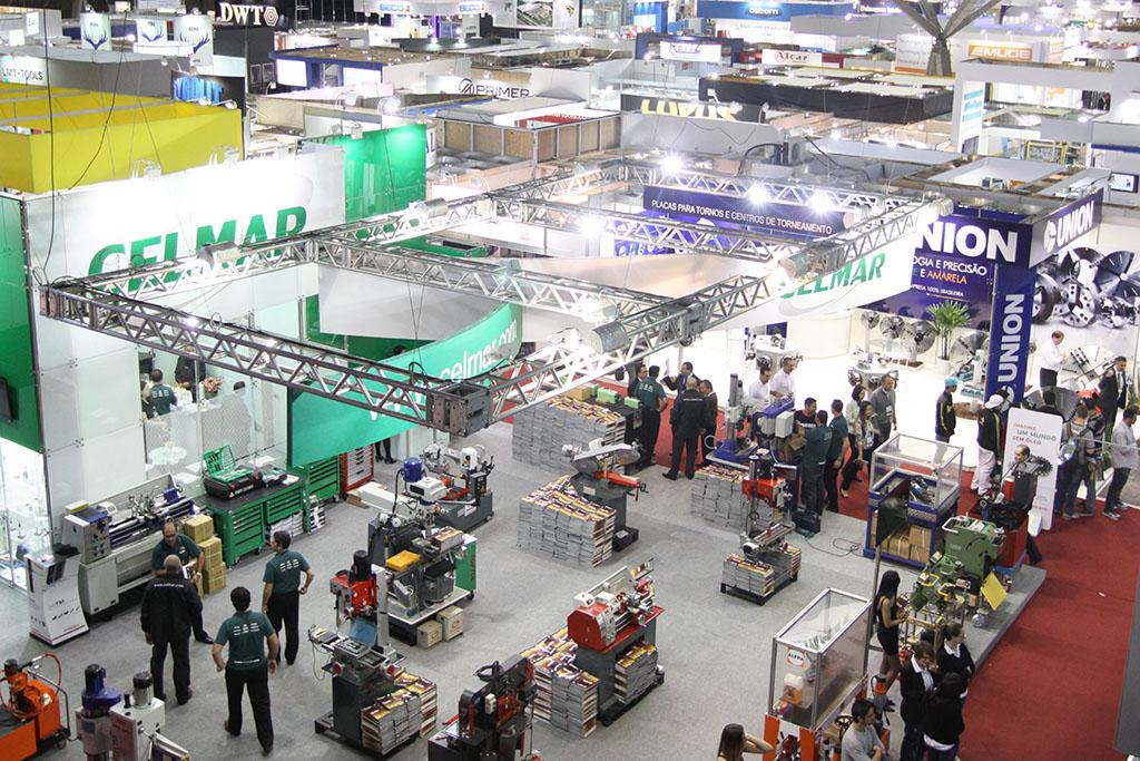 Imagem de cima para baixo. Grande pavilhão de exposições com centenas de estandes de vendas, repletos de vendedores e visitantes.
