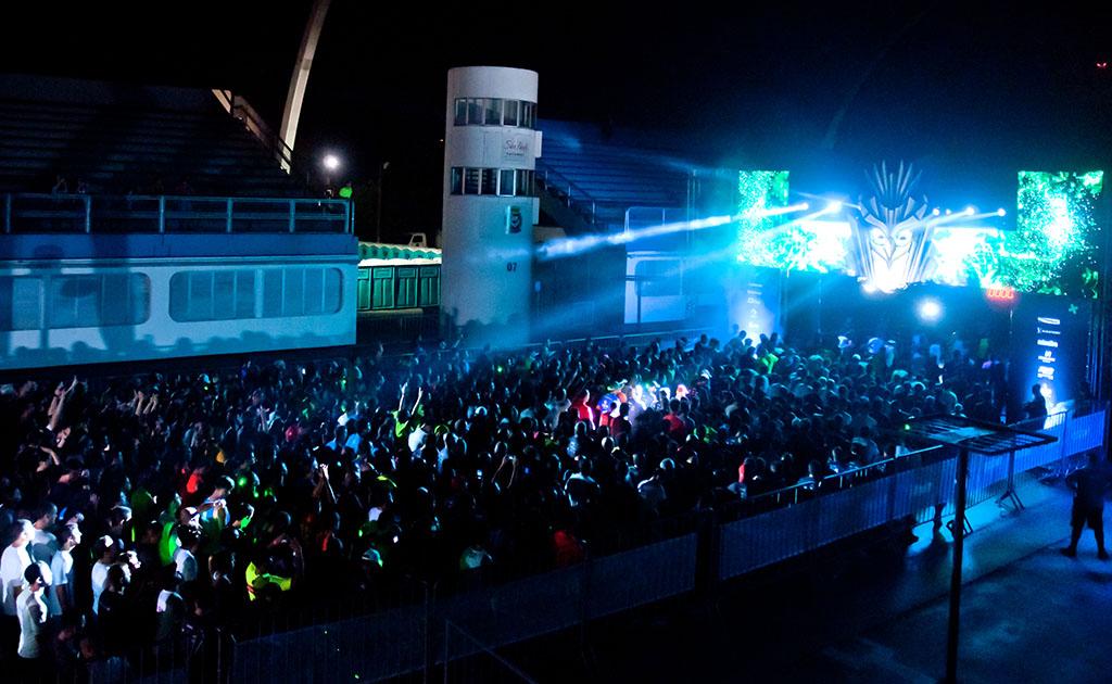 Foto noturna. Em uma área externa, centenas de pessoas em frente a um palco todo iluminado por potentes refletores de luzes azuis.