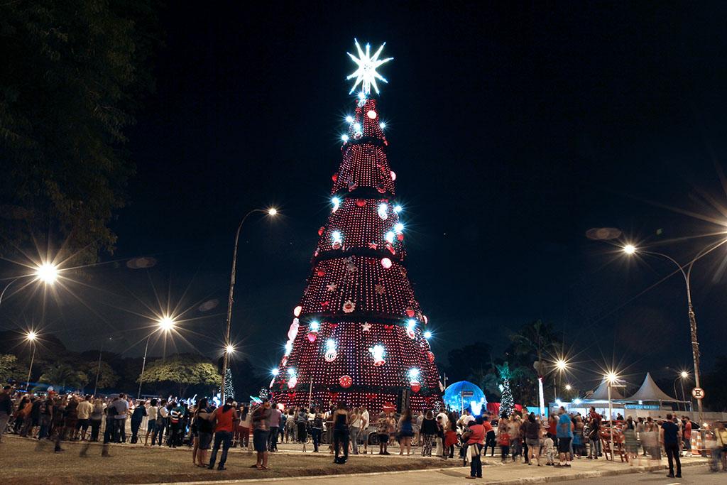 Foto noturna. Em uma grande praça, centenas de pessoas ao redor de uma gigantesca estrutura na forma de uma árvore de natal, toda iluminada por pequenas luzes vermelhas e figuras natalinas. No topo, uma grande estrela iluminada por luz branca.