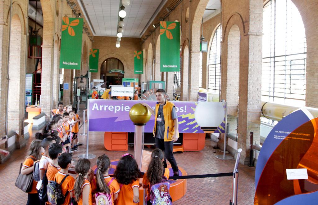 Em um salão com grandes janelas do chão ao teto e de topo arredondado, um grupo de crianças com camisetas cor de laranja assistem a uma palestra sobre eletricidade estática. Na frente do grupo, o palestrante está com sua mão direita apoiada sobre uma grande bola metálica sobre um pedestal.