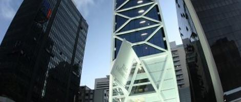 Imagem de baixo para cima. Fachada de um edifício em estilo moderno, formado por grandes estruturas metálicas externas brancas com paredes azuis escuras. Em ambos os lados, um grande edifício comercial com a fachada toda de vidro.