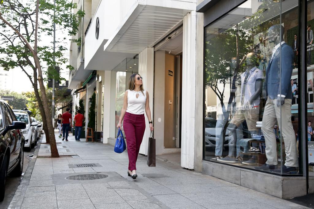 Mulher carregando sacolas de compra caminha por uma calçada bastante larga e plana, com algumas árvores pequenas, em uma rua repleta de lojas. Ela olha para uma grande vitrine do lado direito, onde estão 3 manequins vestindo roupas masculinas. Do lado esquerdo, vários carros estacionados.