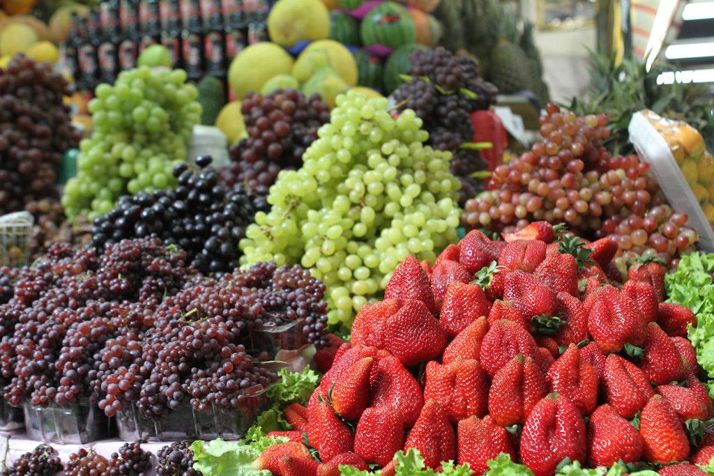 Vários cachos de uva de diversas cores – verdes, vermelhas e roxas, junto com muitos morangos grandes e bem vermelhos.