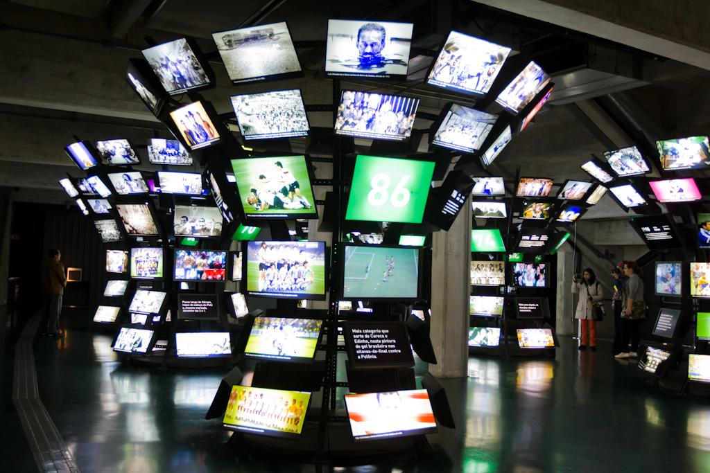 Ambiente escuro. Dezenas de monitores de vídeo dispostos em 4 colunas do chão ao teto, exibem diferentes cenas sobre o futebol. À esquerda, sobre um chão preto, um piso tátil para cegos se estende ao longo do salão.