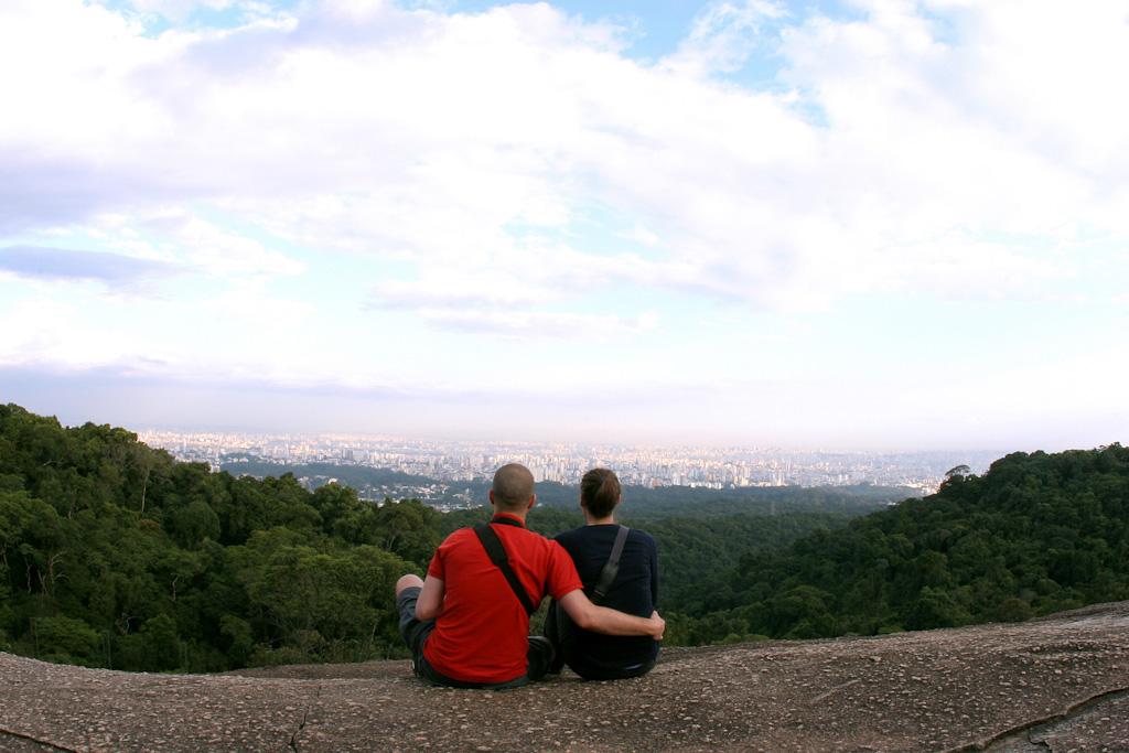 Um casal de costas sentado sobre uma grande rocha, em um local muito alto. Abaixo deles, uma vasta área de mata fechada. No fundo, bem ao longe, parte da cidade.