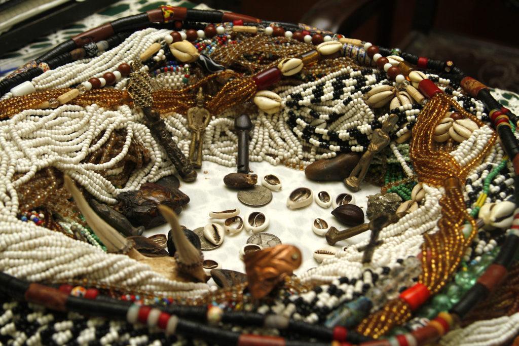 Dezenas de colares de contas multicoloridas e de variadas formas e tamanhos, dispostos sobre uma mesa branca na forma de um quadrado. No centro, alguns búzios e moedas.