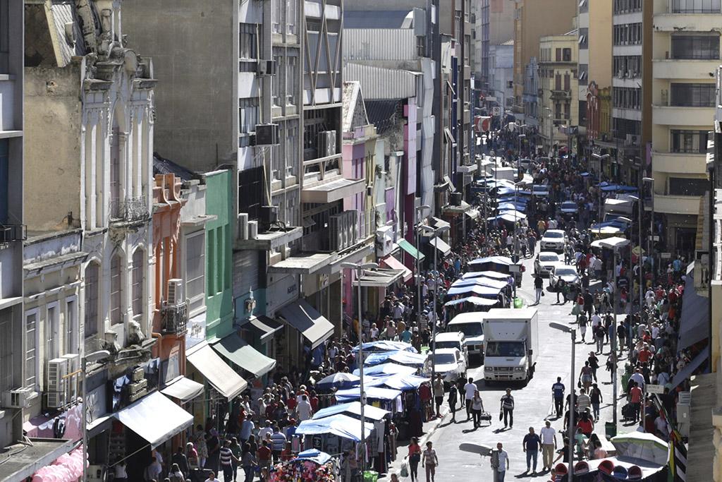 Imagem do alto de uma rua de comércio popular, cercada por inúmeros prédios com lojas no piso térreo. No centro, rua dividida entre veículos e dezenas de barracas de lona azul repletas de mercadorias variadas, lado a lado beirando as calçadas, onde centenas de pessoas caminham.