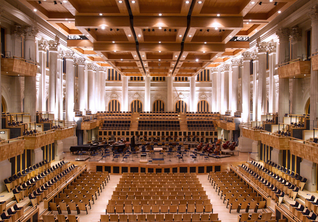 Very large and tall hall. In the center, several rows with dozens of armchairs with light wood back, divided in 3 groups, the central one 3 times greater than the lateral ones. Between the groups, a light floor walkway. On both sides, on floor level, 3 rows of light wood armchairs with black upholstery, arranged laterally. In the levels of the 2 nd and 3 rd floors, several cabins with identical armchairs. To the front, a large stage with several chairs and a grand piano to the left. Behind the stage, 3 more groups of rows of armchairs. At the back of the hall, the walls are all white and ornamented by large columns, illuminated by reflectors of very white light. The ceiling has several acoustic squared elements with lowered bottom, made of light wood and arranged in 5 rows with 3 elements each.