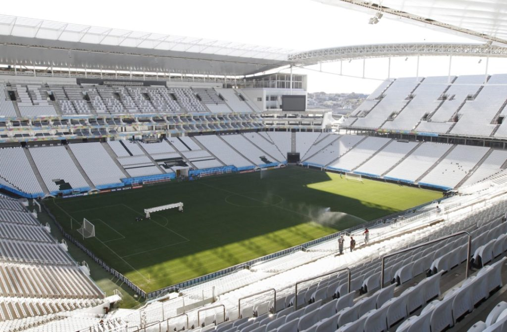 Panoramic photo of the Arena Corinthians depicts the rectangular shape construction in light gray color, with almost open coverage, in a metallic structure. The large bleachers are constructed with precast concrete elements, located to the north, southeast and west, with armchairs arranged side by side in a row. The goal is north and south. In the central part is the vertically striped lawn in two shades of green. In the background, the covered VIP area.