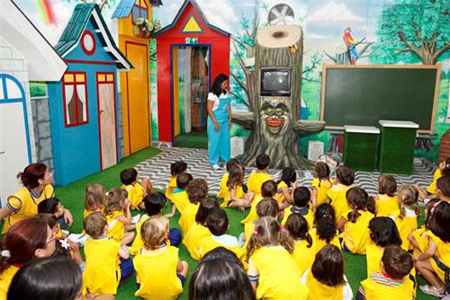 Em uma sala com paredes pintadas com desenhos multicoloridos de casas e florestas com pássaros, várias crianças com camisetas amarelas e sentadas sobre um tapete verde, assistem a uma palestra.