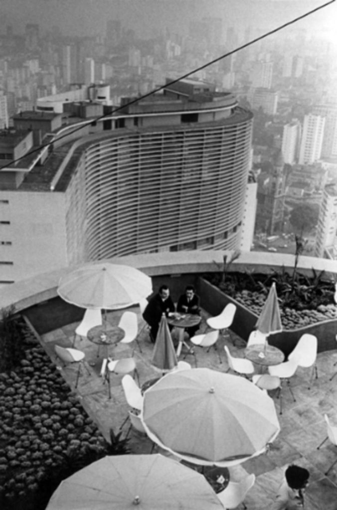 Black and white photo of the top of the building. Part of the terrace with rounded protective wall. Some white chairs and tables with umbrellas. At one of the tables, two men in dark suits are seated. On the sides, 2 small triangular gardens with rocks and some shrubs. In the background, first stand out the top floors and top of the iconic Copan Building, with its revolutionary design in the form of an elongated S-letter. Further down, the city skyline is slightly shrouded in mist.
