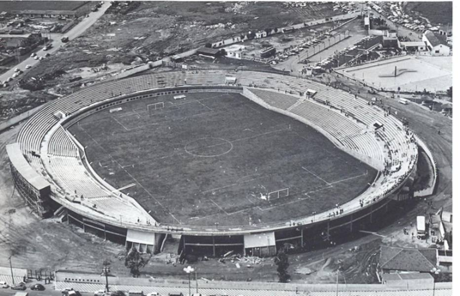 High photo, in black and white. Bleachers in concrete in the shape of a large circle, with some workers scattered. In the center, empty soccer field. On the sides of the field, plus two concrete bleacher structures in the process of finishing. The stadium's surroundings still feature large construction sites.