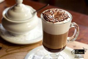 Imagem em close up. Xícara de tamanho médio, toda de vidro transparente e cheia de café com leite. Na superfície, sobre uma espessa espuma clara, um desenho estilizado feito com filetes de chocolate claro e escuro. Do lado esquerdo, um pequeno açucareiro todo branco.