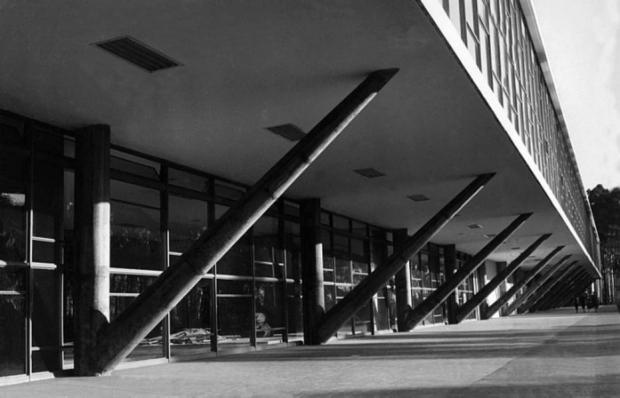 Foto em preto e branco em diagonal, da fachada do museu. Edificação com 2 pisos. O piso inferior, com pé direito bem alto, é mais curto que o superior. Apresenta grandes janelas de vidro emolduradas por estruturas metálicas arredondadas, que vão do chão ao teto e de um lado ao outro do prédio. Possui várias colunas em forma de uma grande letra V, do chão até a laje do piso superior, cuja fachada também é toda coberta por grandes janelas de vidro emolduradas por estruturas metálicas arredondadas, do chão ao teto e de um lado ao outro.