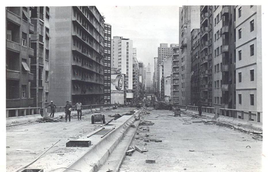 Black and white photo. In the center, quite long, stands out the elevated track of two concrete runways, with works in the final phase. On both sides, placed to each other, several buildings very close to the walls of the road.
