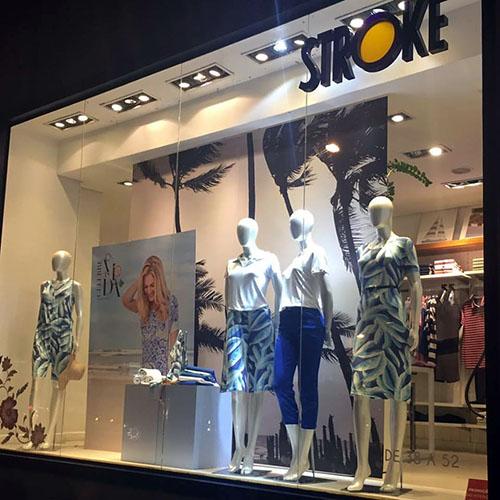 """Vitrine de uma loja com 4 manequins trajando roupas femininas. Da esquerda para a direita, a 1ª está com um vestido curto e estampado sem mangas, nas cores azul marinho, verde claro e branco. A 2ª veste saia igual e blusa branca. A 3ª veste blusa branca e calça azul escuro. A 4ª usa vestido igual à 1ª com mangas curtas. Na parte superior direita da vitrine está o nome da loja """"STROKE"""" em letras pretas."""