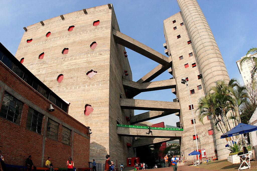 No 1º plano, à esquerda, edificação de um piso toda em tijolos alaranjados aparentes, com 4 grandes janelas. Ao fundo, à esquerda, grande edificação de concreto aparente, sem janelas, com cerca de 12 andares de altura. Na parede frontal, 4 fileiras de elementos vazados. À direita, aproximadamente 10 metros de distância, outra edificação semelhante, porém bem mais estreita. Ambas as estruturas são interligadas por 4 pares de passarelas de concreto aparente, em formato triangular, uma acima da outra. No nível do chão, várias pessoas circulam ao redor. Tudo sob um céu muito azul sem nuvens.