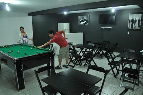 Sala com várias mesas e cadeiras de madeira preta à direita e, à esquerda, duas pessoas jogam em uma mesa de bilhar.