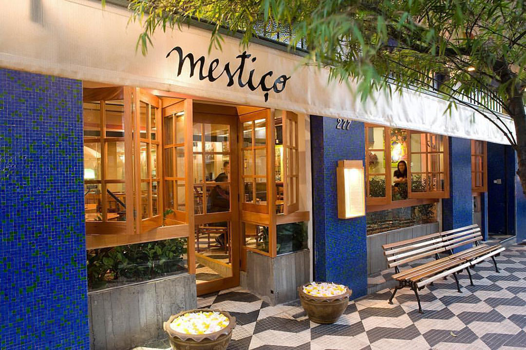 """Restaurant facade with large windows on the side and a door in the center, all with light wood structure and glass. Between them, on both sides and in the center, narrow walls covered by square blue and green pebbles. Above, covering the whole facade, a white awning, where the word """"Mestiço"""" is written in black letters. In front, on the right, a very wide bench made of wooden slats and iron frame (garden bench). The sidewalk in front is decorated by several stylized drawings of a small map of the State of São Paulo, formed by hydraulic tiles, black and white, interspersed, as if it were a great mosaic."""
