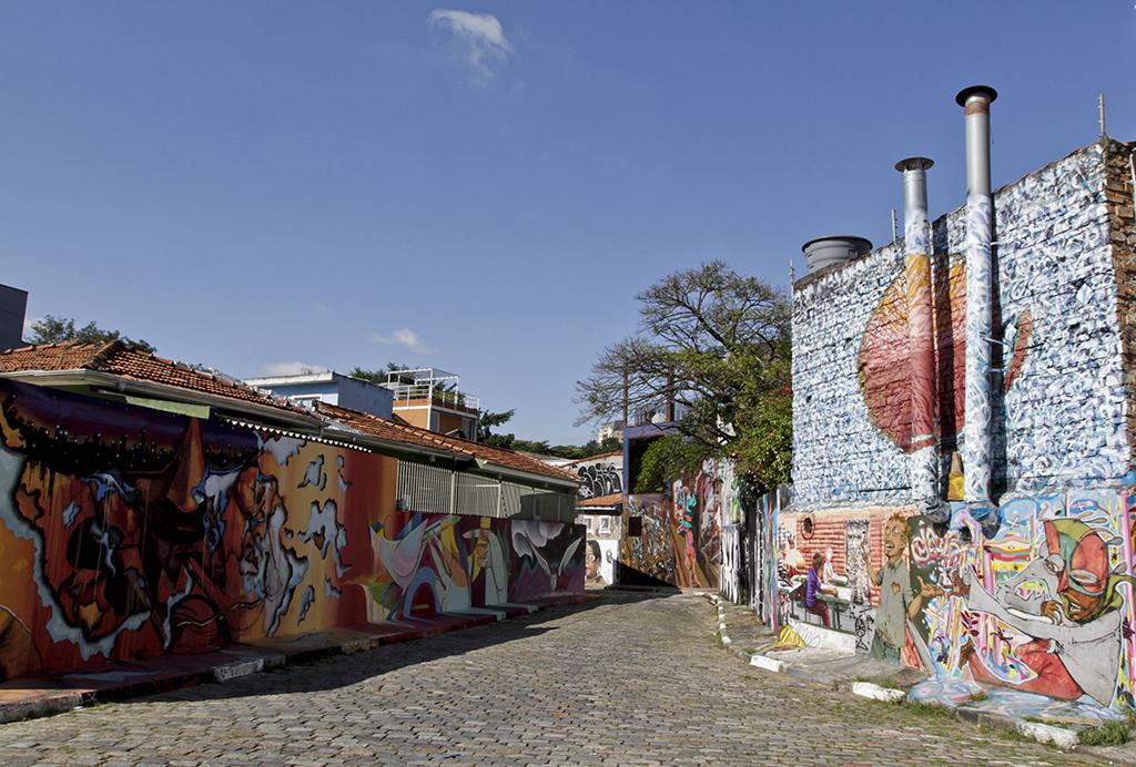 Rua sinuosa de paralelepípedos de pedra. Em ambos os lados, as paredes de diversas casas estão cobertas por grafites multicoloridos. Tudo sob um céu muito azul e sem nuvens.