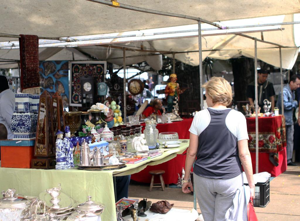 Mulher caminha entre várias barracas de estrutura metálica e teto de lona branca, onde são vendidos diversos objetos de arte e antiguidade como pratarias, vasos, estatuetas, relógios, entre outros.