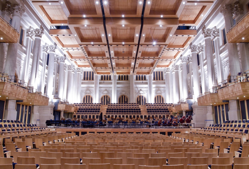 Great concert hall. In the lower rows with hundreds of armchairs with light wood back, arranged in 3 blocks, the middle one being 3 times larger than the later blocks, all separated by light-colored corridors. Next to the walls, 3 rows of side armchairs to the stage arranged in 3 levels. In front of the armchairs, stands a stage in light wood with dozens of musical instruments. In the background, another 3 blocks with rows of armchairs. Above, on the level of a 2nd floor, 3 boxes decorated in light wood on each side with several armchairs. Above, another set of cabins. Still on the sides, further back, walls adorned by several columns lit by strong white light. In the very high ceiling, there are numerous square wooden structures, in the form of boxes, arranged in rows with decreasing height, whose function is to improve the acoustics of the place.