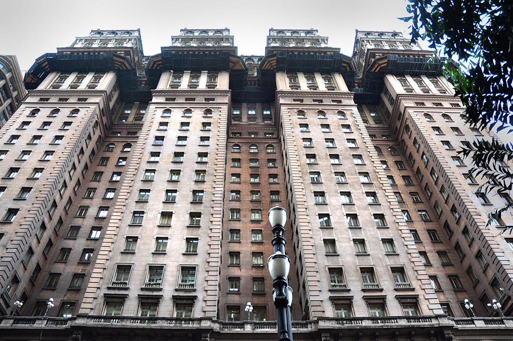 Imagem de baixo para cima, edifício antigo muito alto e largo, marrom claro. Ele é composto por 4 torres com 3 janelões por piso. Entre elas, 3 fachadas recuadas aproximadamente 3 metros, contendo 2 janelões por piso. No topo de cada torre, uma estrutura com 2 pisos no formato de uma residência antiga, com paredes brancas e janelas com molduras azul marinho.