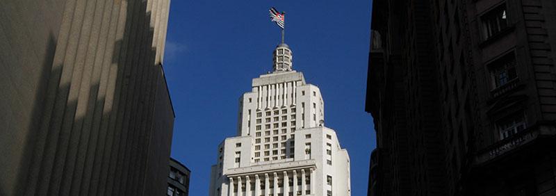 Edificio muy alto, todo blanco, con cientos de ventanas. En los últimos 8 pisos, la estructura queda un poco más estrecha. En la cima, una torre redonda de hormigón y vidrio con altura de 4 pisos y un mástil con la bandera del Estado de São Paulo en la cima. Todo esto bajo un cielo muy azul y sin nubes.