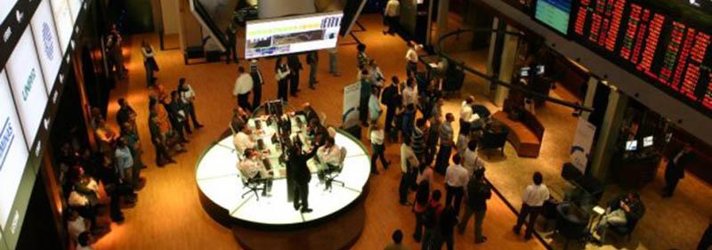 Foto de cima para baixo. Pregão da Bolsa de Valores onde estão dezenas de operadores olhando para um grande painel luminoso vermelho, no alto.
