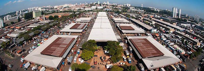 Foto aérea de um centro de comercialização atacadista de perecíveis. Gigantesca estrutura formada por 9 grandes armazéns dispostos em 3 filas, separados por vias com centenas de caminhões.