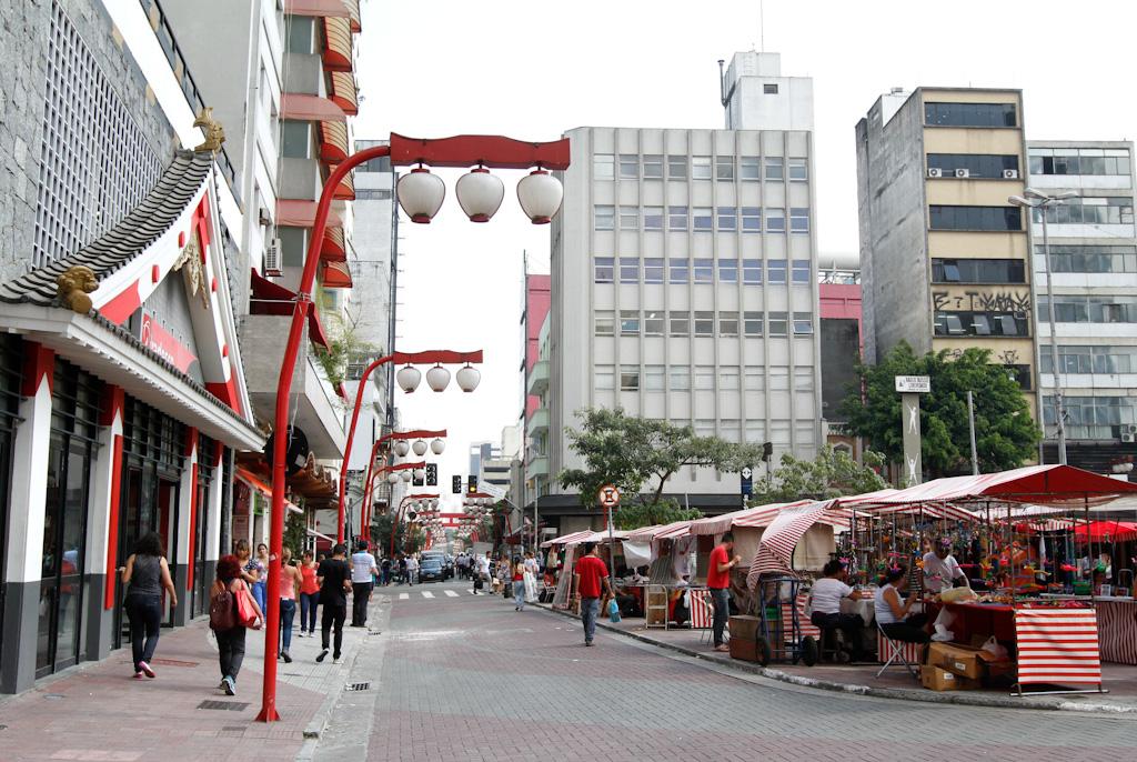 À esquerda, fachada de prédio com elementos arquitetônicos japoneses; várias pessoas caminhando em uma calçada acessível, com diversos postes vermelhos de iluminação, que possuem 3 luminárias brancas no formato de lanternas japonesas. Ao centro, rua transformada em calçadão. À direita, diversas barracas coloridas de flores e artesanato. Ao fundo, vários prédios e algumas árvores.