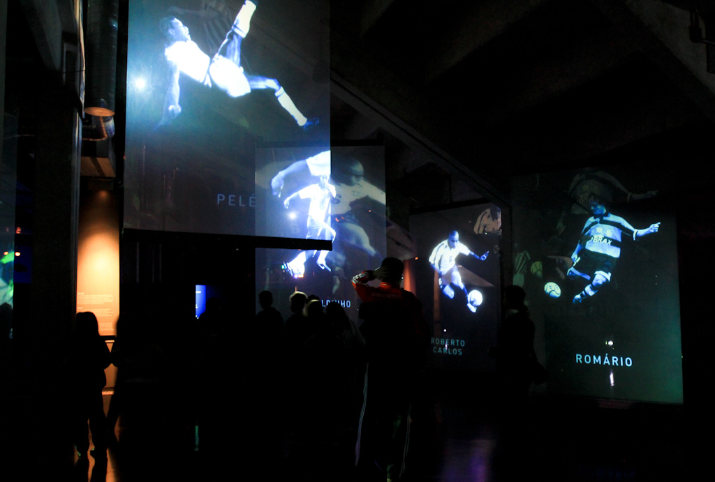 """Internal photo, very dark environment. Four transparent screens, stuck to the ceiling, each one projecting the photo of a football player in action. On the left is the main screen, where is projected the classic photo of the player Pelé performing a play called """"Bicycle"""", where the athlete is in the air, with the whole body horizontal, the right arm slightly pointed down. The right leg is stretched up, after hitting the ball in full."""