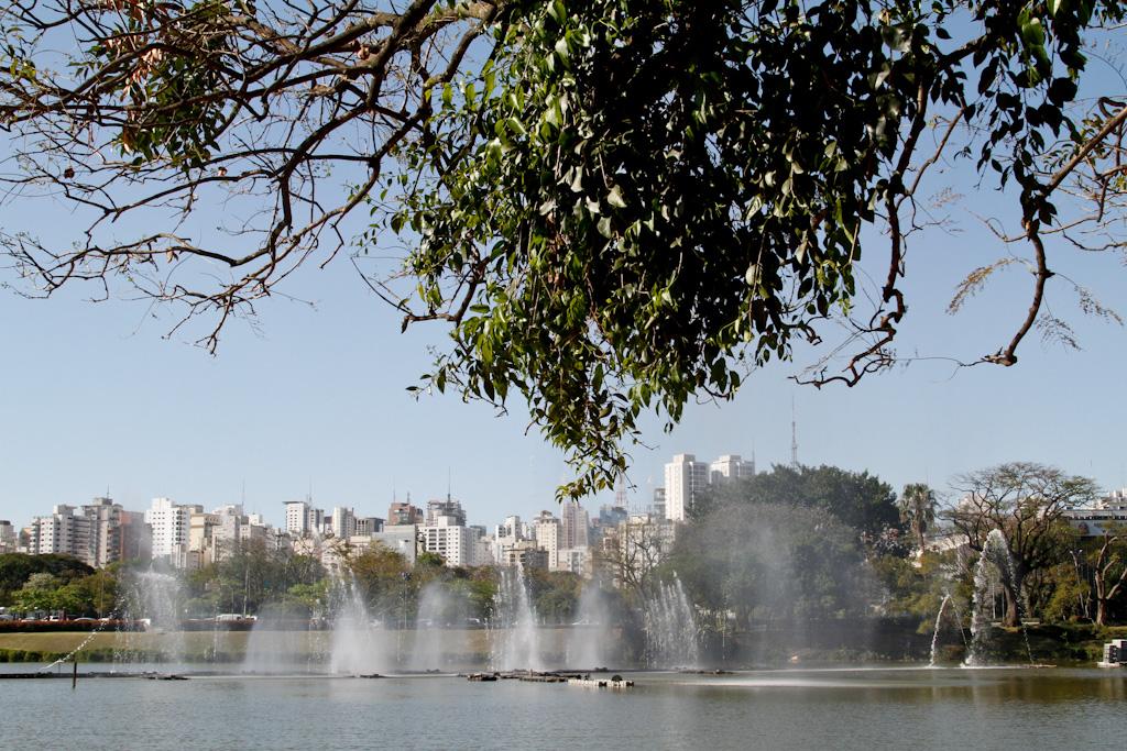 Grande lago com um grande chafariz no centro, em um dia muito ensolarado. Bem ao fundo, a skyline da cidade.