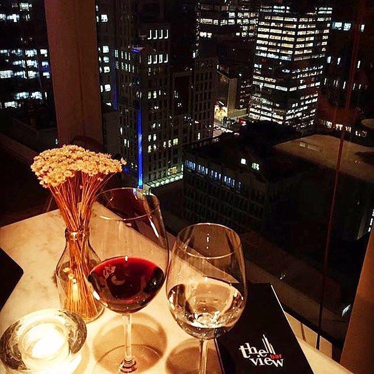 """À esquerda, sobre uma mesa mármore bege claro iluminada por um foco de luz, 2 taças de cristal, sendo uma com vinho tinto outra com vinho branco. Do lado esquerdo um pequeno vaso de vidro transparente com florzinhas amarelas. Do lado direito, um cardápio com capa preta e as palavras """"The View Bar"""" impressas com letras brancas. A mesa está encostada em uma grande janela de vidro, por onde se vê do alto vários prédios com janelas acesas."""