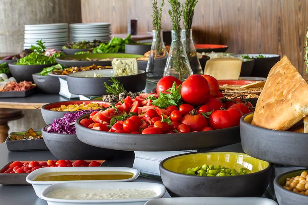 Sobre uma mesa com tampo cinza, buffet de saladas. Várias tigelas cinzas de tamanhos variados com verduras, tomates, queijos e pães. Ao fundo, duas pilhas de pratos.